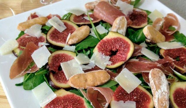 Carpaccio de figues au jambon ibérique, flocons de parmesan, roquette et vinaigrette à la pistache.